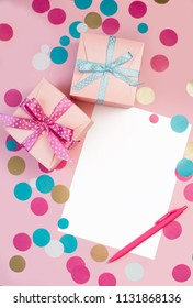Decorated boxes, confetti and blank white sheet of paper as a concept of holiday gifts and congratulations.
