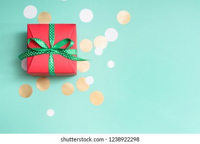 Decorated boxes and confetti on the green background as a concept of holiday gifts and congratulations.