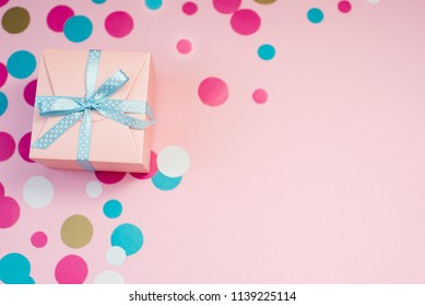 Decorated boxes and confetti on the pink background as a concept of holiday gifts and congratulations.