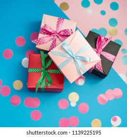 Decorated boxes and confetti on the pink and blue background as a concept of holiday gifts and congratulations.