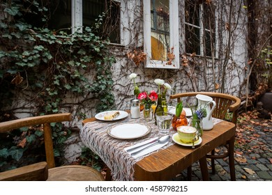 A decorated breakfast table with coffee, boiled egg, orange juice and strudel at outdoor terrace during autumn. Side view