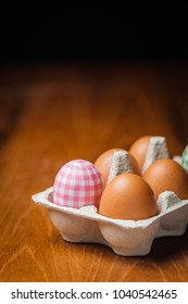 Decorated and brown hen eggs in cardboard box.