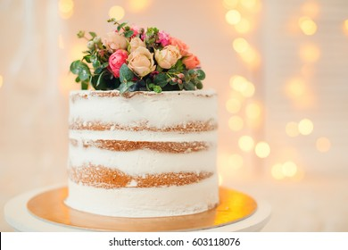 Decorated by flowers white naked cake, rustic style for weddings, birthdays and events.