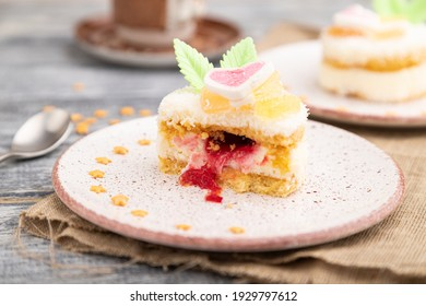 Decorated cake with milk and coconut cream with cup of coffee on a gray wooden background and linen textile. Side view, close up, selective focus.