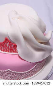 Decorated Cake: two tiers pink and white cake, with ruffles decoration and edible lily flower made from sugar paste - details of the ruffle before flower added