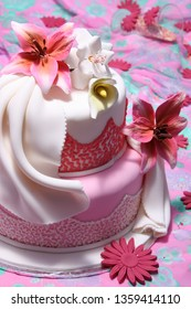Decorated Cake: two tiers pink and white cake, with ruffles decoration and edible lily flower made from sugar paste