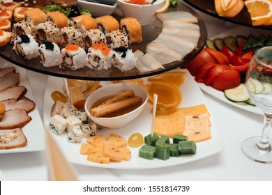 Decorated catering banquet table with different sushi rolls and sushi plate assortment on a party. Food for party. Delicious cuisine menu in tasty food restaurant. Table for banquets, weddings, partie