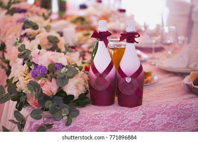 Decorated champagne bottles, candles and flowers on Wedding table with decorations in restaurant.