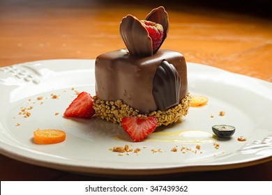 Decorated chocolate dessert on white plate