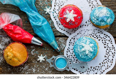 Decorated Christmas cupcakes on a wooden background, top view