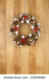 Decorated christmas door wreath with birch stars, cinnamon sticks, anise stars and pine cones brown twigs on sapele wood background, copy space