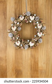 Decorated christmas door wreath with birch hearts and white painted pine cones brown twigs on sapele wood background, copy space