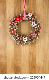 Decorated christmas door wreath with red and white pillow stars brown twigs gingham and polka dot on sapele wood background, copy space