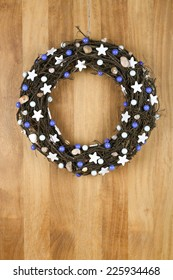 Decorated christmas door wreath with white stars and blue pearls brown twigs on sapele wood background, copy space