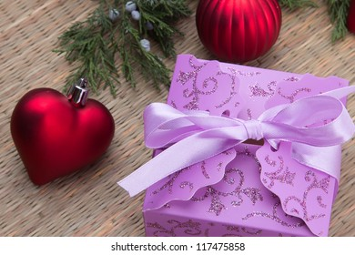 Decorated Christmas purple gift box with red ball and heart. Decorative christmas composition on wood table