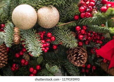 Decorated Christmas tree. Bright decorations for the New Year. Christmas decoration. Gold balls, red berries and ribbons, cones decorate the Christmas tree. Christmas decoration.  New Year's greetings