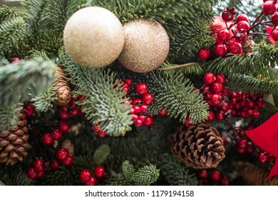Decorated Christmas tree. Bright decorations for the New Year. Christmas decoration. Gold balls, red berries and ribbons, cones decorate the Christmas tree. Christmas decoration. New Year's greetings.