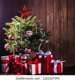 Decorated Christmas tree with candy canes , star , striped baubles and gift boxes on wooden background
