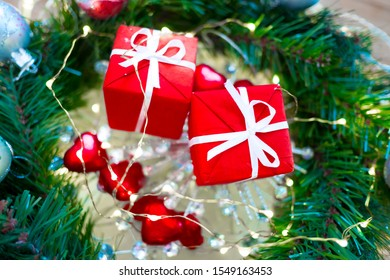 Decorated Christmas tree closeup with red Christmas gifts with white ribbon, heart-shaped sweets and a lot of lights, glitter and blurred bokeh background