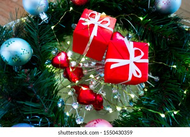 Decorated Christmas tree closeup with red Christmas gifts with white ribbon, heart-shaped sweets and a lot of lights, glitter and blurred bokeh