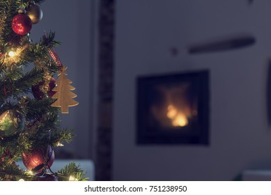 Decorated Christmas tree in front of a burning fire in a wall insert in the darkness of Christmas Eve in a cosy family home.