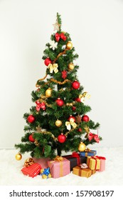 Decorated Christmas tree with gifts on grey wall background