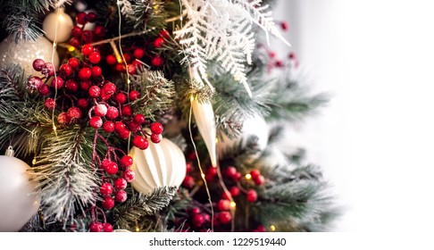 Decorated Christmas tree with lights and white background.