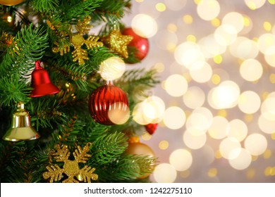 Decorated Christmas tree on soft yellow lights with bokeh effect background. Festive composition with fir and blurry sparkling backdrop, new year holiday decorations. Close up, copy space.