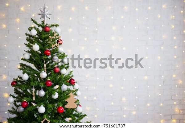 decorated christmas tree over white brick wall with shiny lights