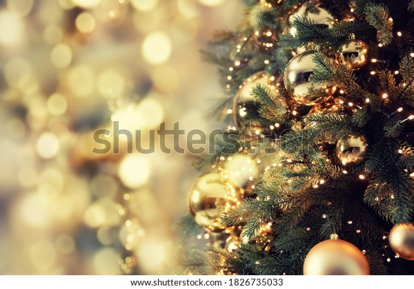 Decorated christmas tree pine on blurred gold background bokeh light banner.