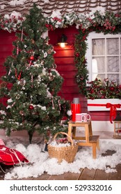 Decorated Christmas tree with presents on the porch and hot tea in cups and thermos