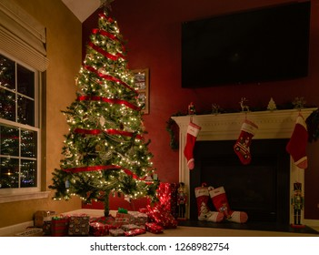 Decorated Christmas tree with presents underneath and stockings by fireplace.