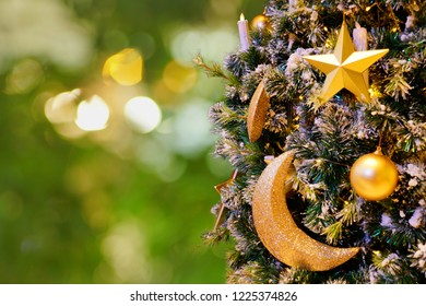 Decorated christmas tree with shiny balls, star, crescent moon and light bulbs on blurred green light background.