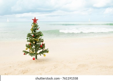 Decorated Christmas tree standing on the sand with ocean and sailboats in the background