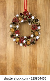 Decorated christmas wreath with red and white pillow hearts brown twigs walnuts and pine cones on sapele wood background, copy space