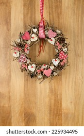Decorated christmas wreath with red and white pillow hearts brown twigs gingham and polka dot on sapele wood background, copy space