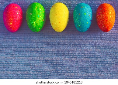 Decorated colorful Easter eggs on blue knitted background with space for text. Trendy minimal pop art style and colors.