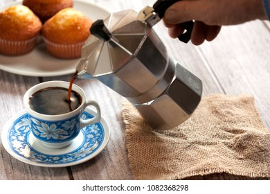 decorated cup of coffee, muffins on plate and coffeemaker pouring coffee into a cup on wood table and burlap