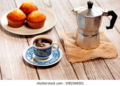 decorated cup of coffee, muffins on plate and coffeemaker on wood table and burlap
