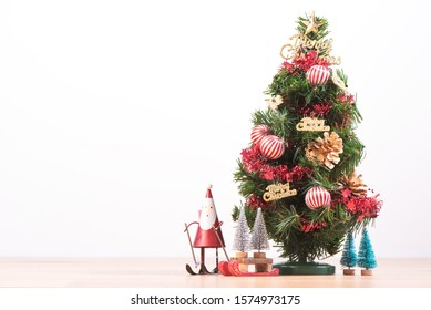 Decorated cute Christmas tree on a wooden floor with white background and toys, blank for festive design concept, close up.