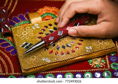 Decorated diary with pen Rajasthani handicraft Jaipur India.Child holding pen in hand to write in book adorned with lovely mirror and beads work . handy golden diary, pretty red pen. small secret book