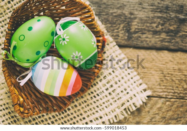 Decorated Easter eggs in basket on wooden background