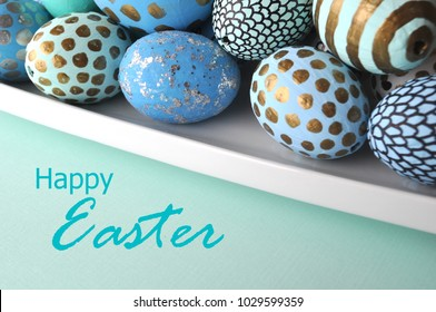 Decorated Easter eggs blue gold turquoise on solid mint background with a teal Happy Easter lettering sign for greeting cards.