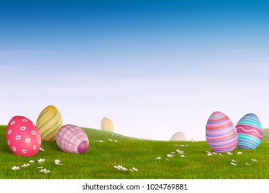 Decorated Easter eggs lying in the grass in a hilly landscape.