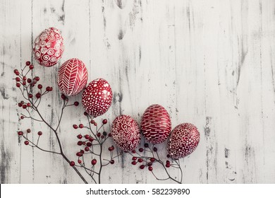 Decorated Easter eggs using a traditional in Eastern Europe wax-resist method and modern patterns. Still life with Pysanka, dry plants and lace on whitewashed wooden background, top view, copy space