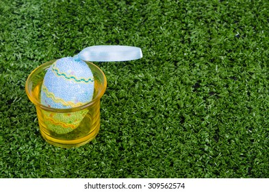 Decorated egg in yellow glass on the green grass