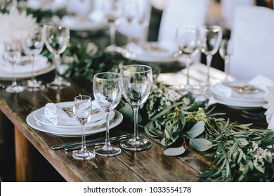 Decorated elegant wooden wedding table in rustic style with eucalyptus and flowers, porcelain plates, glasses, napkins and cutlery. Horizontal