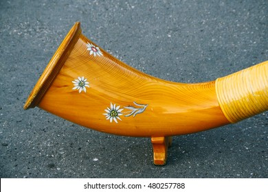 The decorated end of an alphorn, Switzerland's traditional music instrument. The decorative motif is the edelweiss flower, symbol of the Alpine mountains.