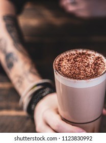 A decorated females arm wearing leather bracelets is holding a glass of hot chocolate with a frothy top.