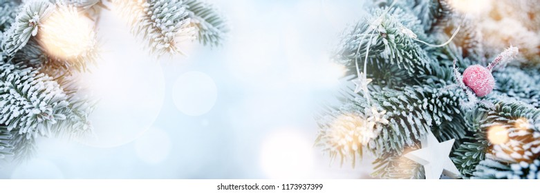 Decorated fir branches at christmas time in winter on abstrakt blue bokeh background